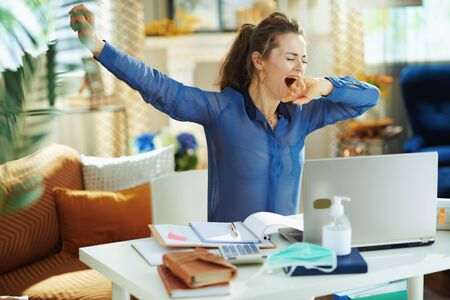 tired young woman in blue blouse at modern home in sunny day yawing in temporary home office during the coronavirus epidemic.