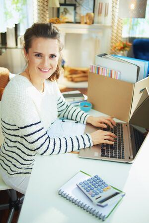 smiling modern 40 years old business woman in striped sweater in temporary home office in the modern house in sunny day working.