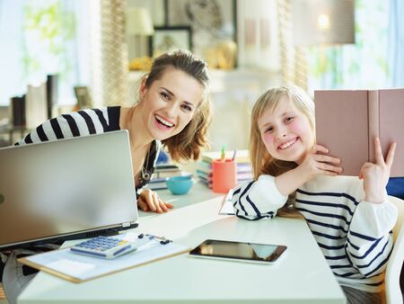 Portrait of smiling young mother and daughter in striped sweaters in home office at modern home in sunny day working and doing homework. Stock Photo