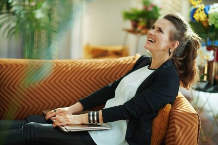 relaxed stylish woman in white blouse and black jacket with closed laptop sitting on sofa in the modern living room in sunny day.