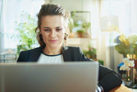 élégante femme au foyer d'âge moyen en blouse blanche et veste noire dans la maison moderne en journée ensoleillée surfer sur le web sur un ordinateur portable tout en étant assis sur un canapé.