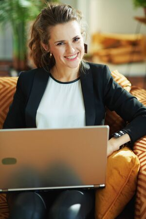 happy trendy middle age housewife in white blouse and black jacket at modern home in sunny day reading text on a laptop while sitting on couch. Stock fotó