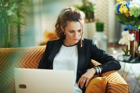 pensive young female in white blouse and black jacket in the modern living room in sunny day reading on a laptop while sitting on couch. Stock fotó
