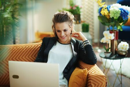 smiling elegant female in white blouse and black jacket in the modern living room in sunny day editing on a laptop while sitting on couch.