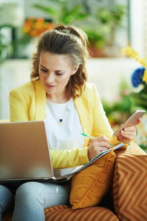 smiling modern student woman in jeans and yellow jacket with laptop and smartphone study online at modern home in sunny day. Stock fotó