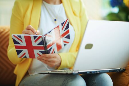 Closeup on female in jeans and yellow jacket with laptop taking notes with a pen in a UK flag notebook in the living room in sunny day. Reklamní fotografie