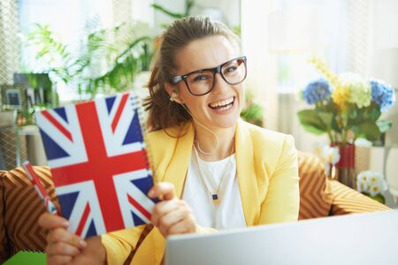 happy trendy student woman in jeans and yellow jacket with laptop showing UK flag notebook in the modern house in sunny day.