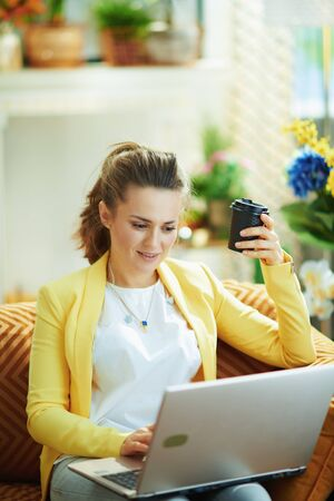 happy young female in jeans and yellow jacket at modern home in sunny day learning online on a laptop.