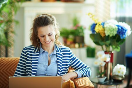 smiling modern 40 years old woman in blue blouse and striped jacket sitting on divan with laptop in the modern living room in sunny day.