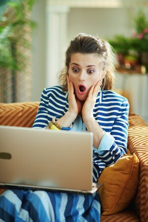 shocked modern female in blue blouse and striped jacket sitting on couch with laptop in the modern house in sunny day. Stock Photo