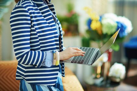 Closeup on woman in blue blouse and striped jacket at home in sunny day using laptop.