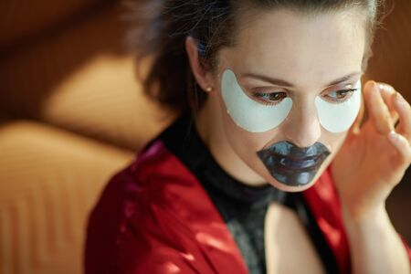 modern 40 years old woman in black body lingerie and red bathrobe in the modern house in sunny day using black hydrogel lip mask and eye mask.