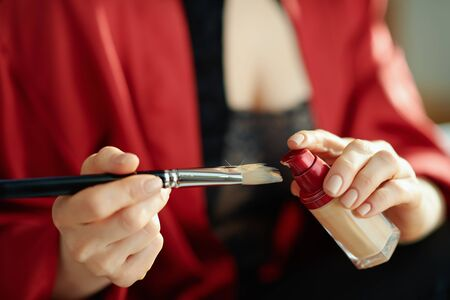 Closeup on woman in the living room in sunny day putting liquid foundation on cosmetic brush. Banque d'images