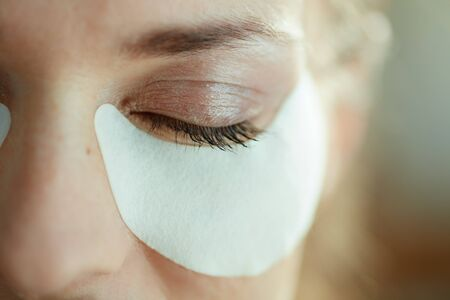 Closeup on woman in the house in sunny day using white cotton eye patches.