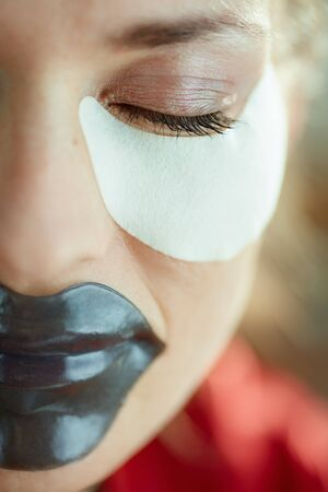 Closeup on woman in the house in sunny day using hydrogel lip mask and eye mask.