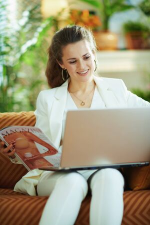 smiling modern middle age woman in white blouse and jacket with laptop and magazine at modern home in sunny day. Foto de archivo