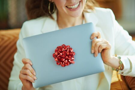 Closeup on happy woman and gift laptop with red bow in the house in sunny day.