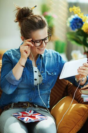 happy young female in jeans shirt with tablet PC and UK flag notebook learning foreign language online in the modern house in sunny day.