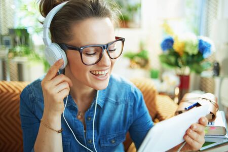 happy middle age housewife in jeans shirt with white headphones and tablet PC study online in the modern house in sunny day.
