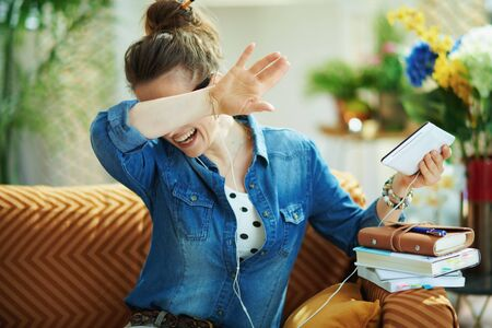 happy young housewife in jeans shirt with white headphones and tablet PC rejoicing while study online in the modern living room in sunny day. Banque d'images