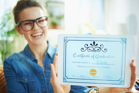 Closeup on happy woman in jeans shirt in the house in sunny day showing electronic Certificate of Graduation on tablet PC screen.