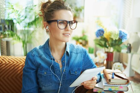 pensive 40 years old housewife in jeans shirt with white headphones and tablet PC study online in the modern house in sunny day.