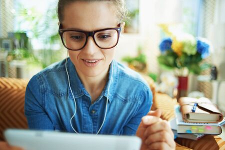 happy stylish housewife in jeans shirt with white headphones and tablet PC study online in the modern living room in sunny day.