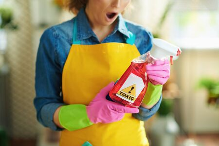Closeup on shocked woman in orange apron and pink rubber gloves with spray bottle of cleaning supplies reading instruction in the house in sunny day. toxic cleaning supplies concept.