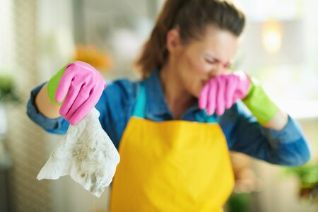 Closeup on disgusted woman in orange apron and pink rubber gloves at home in sunny day showing dirty wet wipe.