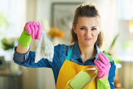 disgusted modern 40 years old woman in orange apron and pink rubber gloves with spray bottle of cleaning supplies showing dirty wet wipe in the modern living room in sunny day.