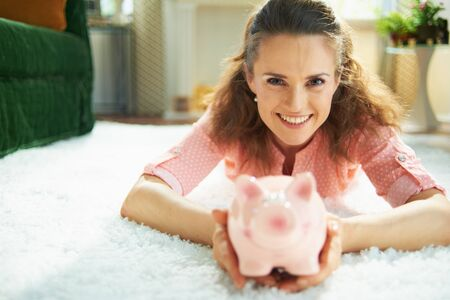 Portrait of happy modern housewife in blouse and white pants with piggy bank while laying on white carpet in the modern living room in sunny day.