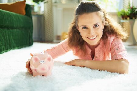 Portrait of smiling young woman in blouse and white pants with piggy bank while laying on white carpet at modern home in sunny day. Stock Photo