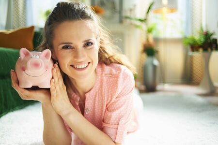 Portrait of smiling young woman in blouse and white pants with piggy bank while laying on white carpet in the modern house in sunny day.