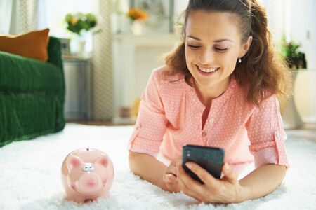 smiling young housewife in blouse and white pants with piggy bank searching for carpet cleaning service on a smartphone while laying on white carpet at modern home in sunny day.