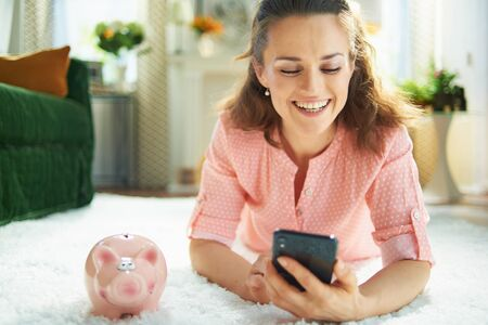 smiling young woman in blouse and white pants with piggy bank searching for carpet cleaning service on a smartphone while laying on white carpet in the modern living room in sunny day. Stock Photo
