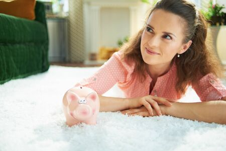 happy modern 40 years old housewife in blouse and white pants with piggy bank while laying on white carpet in the modern house in sunny day.
