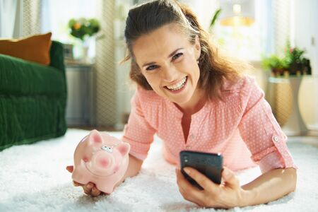 Portrait of smiling modern woman in blouse and white pants with piggy bank searching for carpet cleaning service on a smartphone while laying on white carpet at modern home in sunny day. Stock Photo