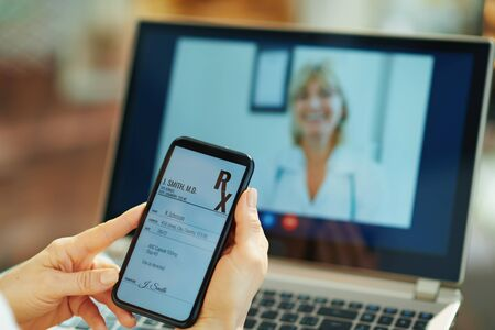 Closeup on woman with electronic rx on a smartphone and doctor on video call on a laptop in background in the house in sunny day.