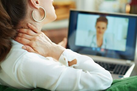 Seen from behind woman in white blouse with neck pain speaking with doctor using tele health technology in the living room in sunny day.