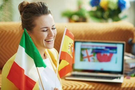 happy trendy 40 years old woman in yellow jacket with flags learning foreign language online on a laptop in the modern living room in sunny day.