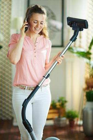happy modern woman in blouse and white pants with vacuum cleaner speaking on a smartphone in the modern house in sunny day.