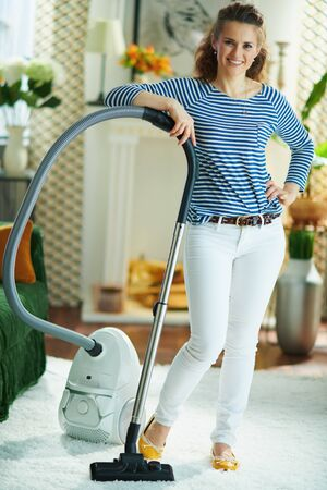 Full length portrait of happy modern female in striped t-shirt and white pants with vacuum cleaner in the modern living room in sunny day. 스톡 콘텐츠