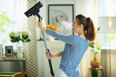 cheerful young female in striped t-shirt and white pants with vacuum cleaner doing housework at modern home in sunny day.