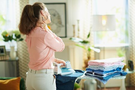 Seen from behind woman in pink shirt and white pants with pile of folded ironed clothes having neck pain while ironing on ironing board in the living room in sunny day. Reklamní fotografie