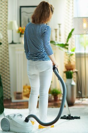 Seen from behind female in striped t-shirt and white pants in the living room in sunny day vacuuming white fluffy carpet.