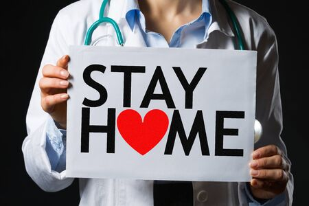 Closeup on medical doctor woman showing blank billboard with stay home sign isolated on black