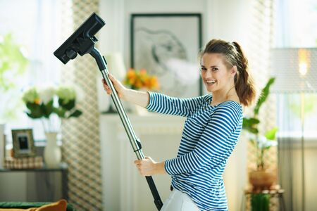 smiling young woman in striped t-shirt and white pants with vacuum cleaner in the modern house in sunny day. 스톡 콘텐츠
