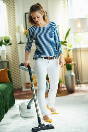 Full length portrait of modern middle age housewife in striped t-shirt and white pants at modern home in sunny day vacuuming white fluffy carpet.