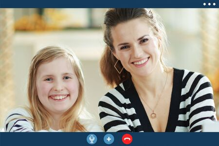 Video call screen of smiling young mother and daughter in striped sweaters in the modern living room in sunny day.