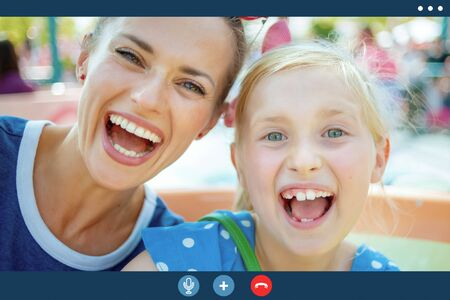 Video call screen of smiling mother and child outdoors